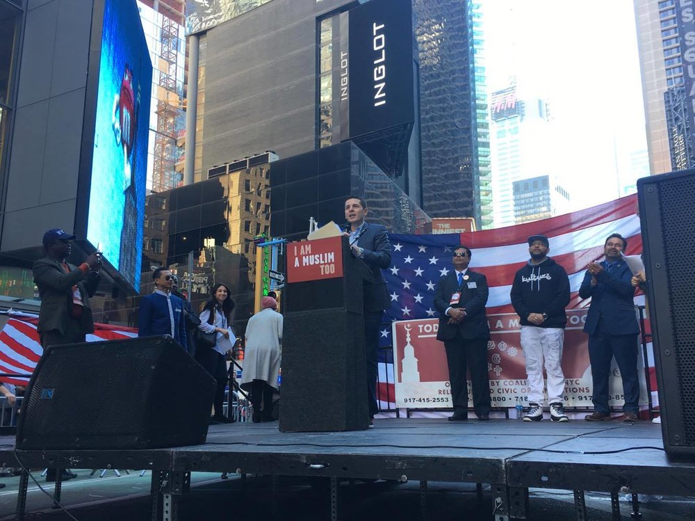 Comedian Dean Obeidallah introduces a speaker, Times Square.