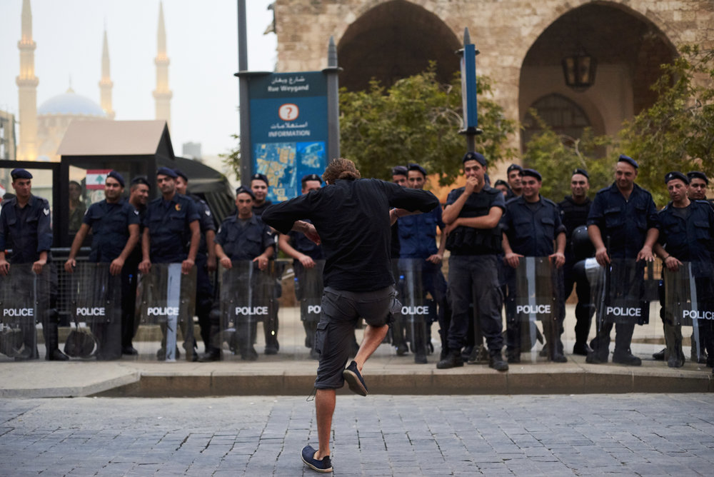 """A man dance in front of riot police officers during a """"You Stink"""" rally in Downtown Beirut, Lebanon, August 2015."""