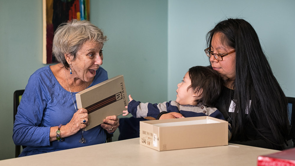 Volunteer Betsy Grob delights mother and baby as they set about creating an educational toy out of a common shoe box.