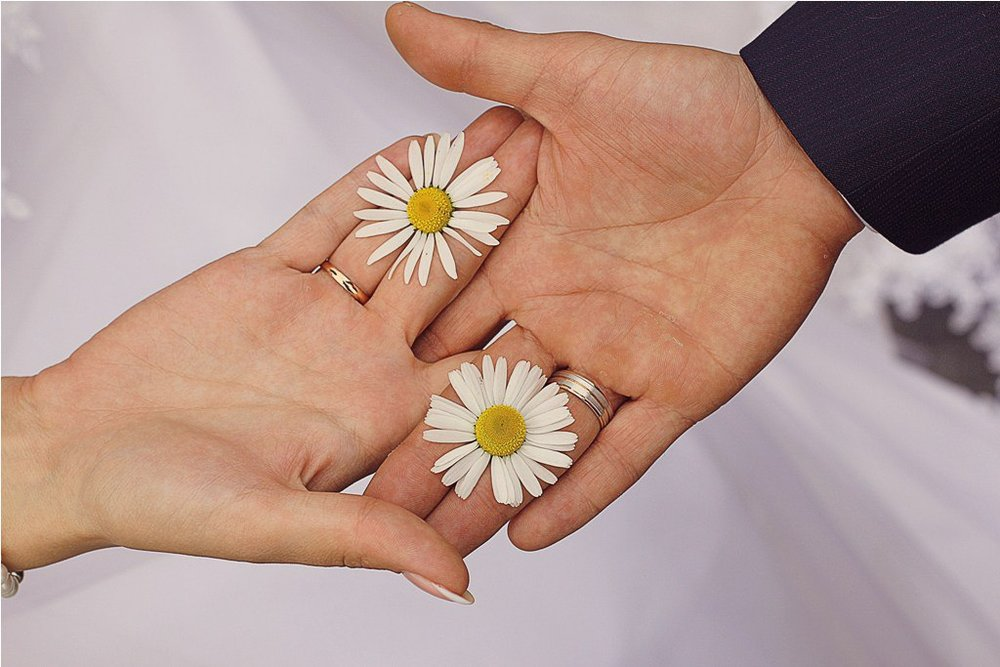 Norilsk - Hands of a Young Russian Couple holding two Flowers