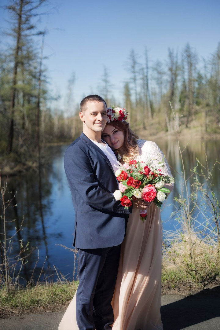 Norilsk people - Couple married holding a bouquet of flowers by a river
