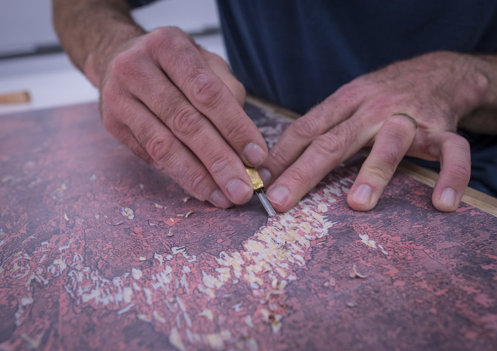 "Todd Anderson, assistant professor of art and printmaking at Clemson University, carves out a ""stamp"" to create a reductive woodcut print of a glacier for ""The Last Glacier"". (Photo by Ken Scar)"