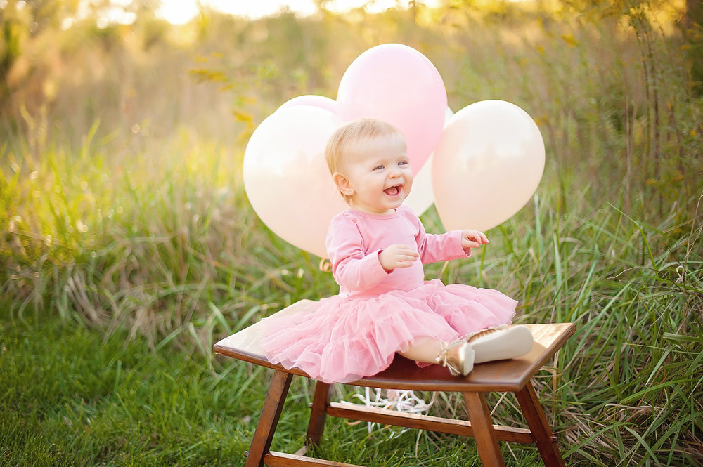 giggling laughing one year baby girl birthdya phtoo shoot outdoors sunset greensboro north carolina with pink balloons and tutu.jpg