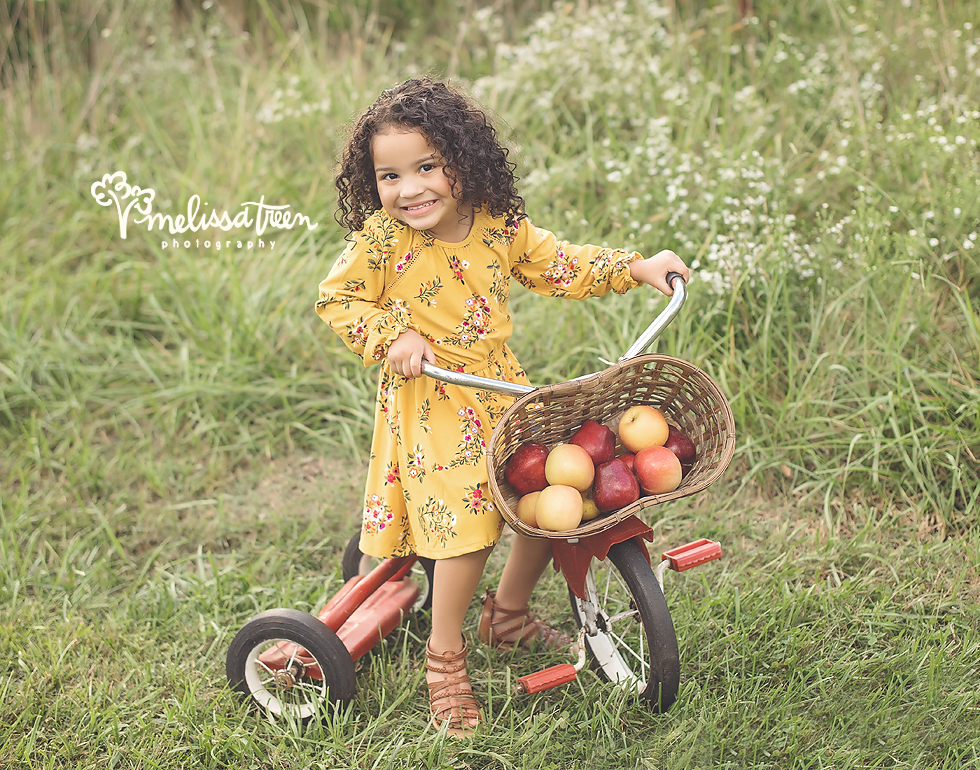 little-girl-on-bike-with-apple-basket-family-photographer-greensboro-chapel hill-burlington.jpg