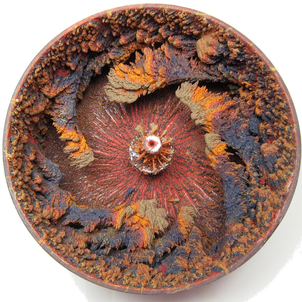 Self Assembly - A spray of molten wax accumulates on the rim of a rotating wheel.
