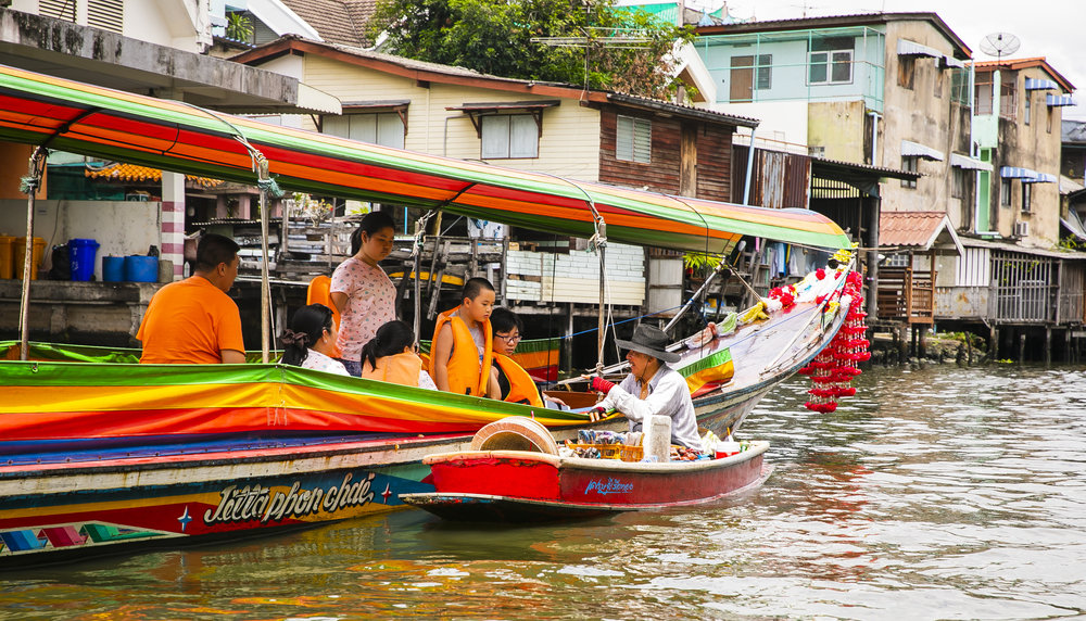 """Take the scenic route by hopping on a long-tail boat. Your driver will stop by a """"floating market"""" and you can buy drinks and trinkets. Just beware of the price gouging and haggle for your life."""