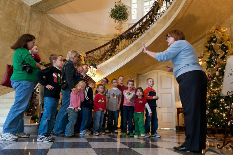Volunteer docent, Lynda Hargroder, gives a tour to young children at the Old Governor's Mansion.