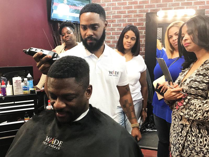 Wade Menendez resurrects a client's hair. (Maquita Peters/NPR)