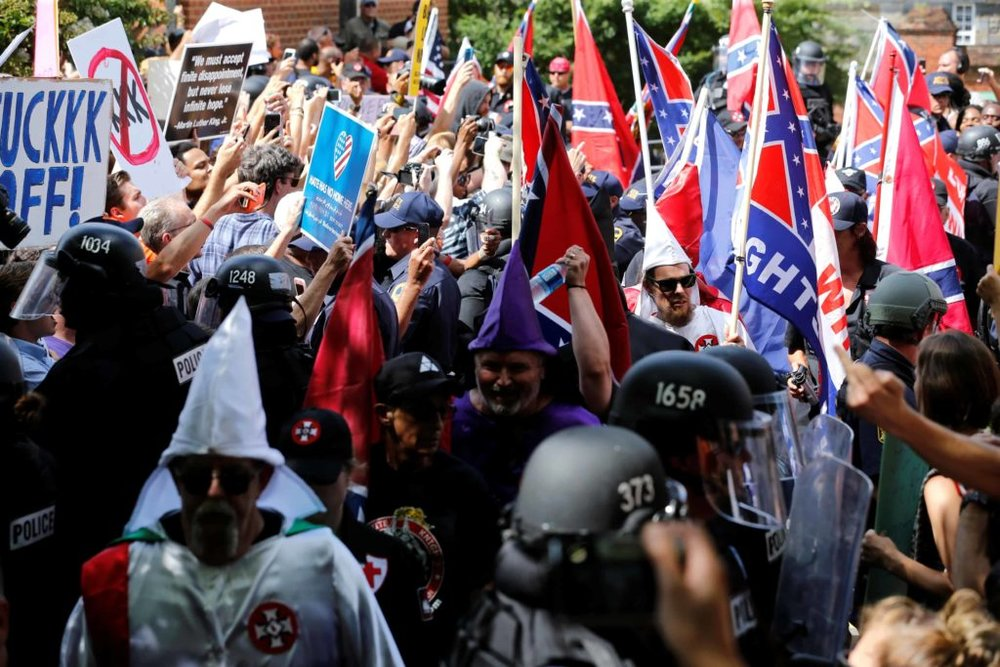 Racists get out their finest sheets and Confederate flags for white supremacy rally amongst a small gathering of police officers. (google.com)
