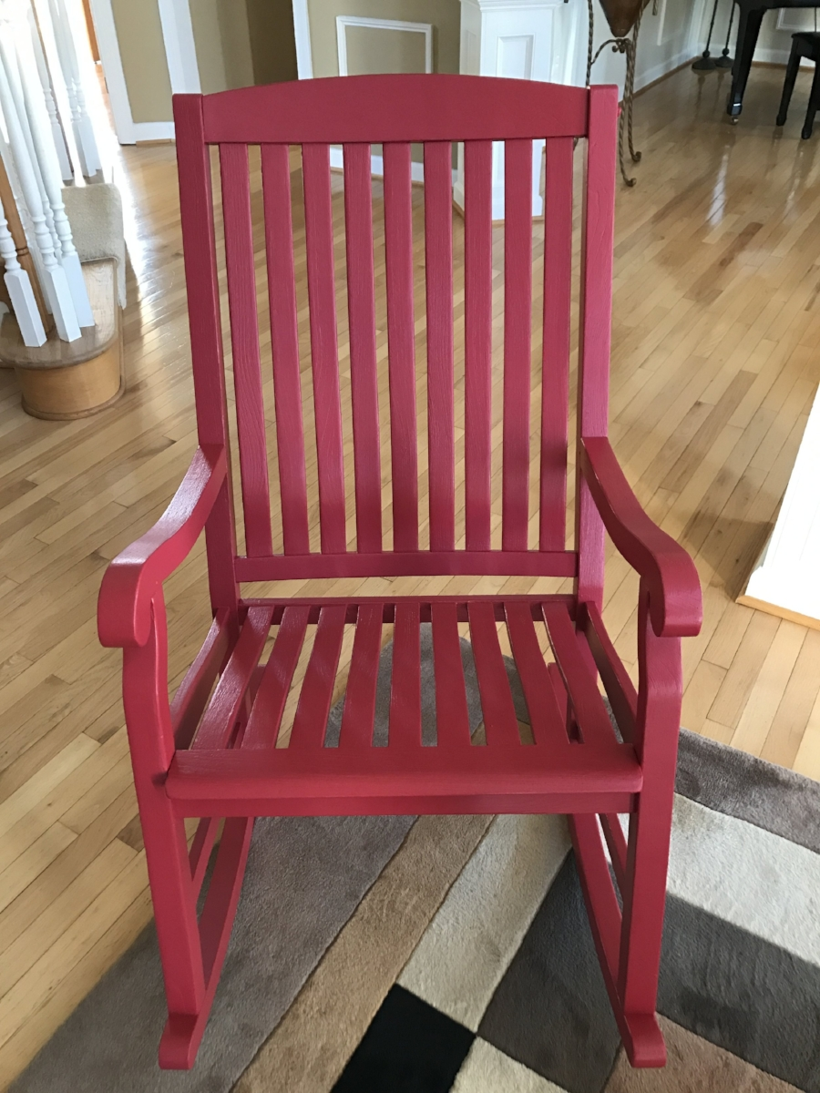 After: We sanded the old varnish off and repainted with a red stain, leaving our clients with a like new chair to relax in, and one less item in the land fill.