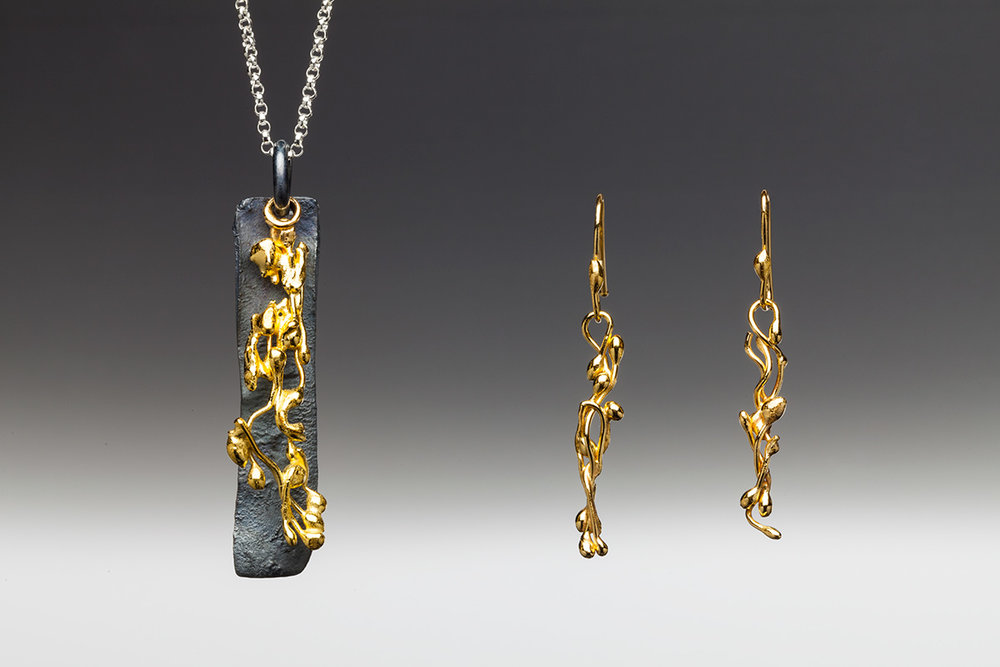 22k gold and oxidized sterling silver with 18 inch sterling silver chain. Vine earrings and Vine Pendant with Oxidized Backdrop.