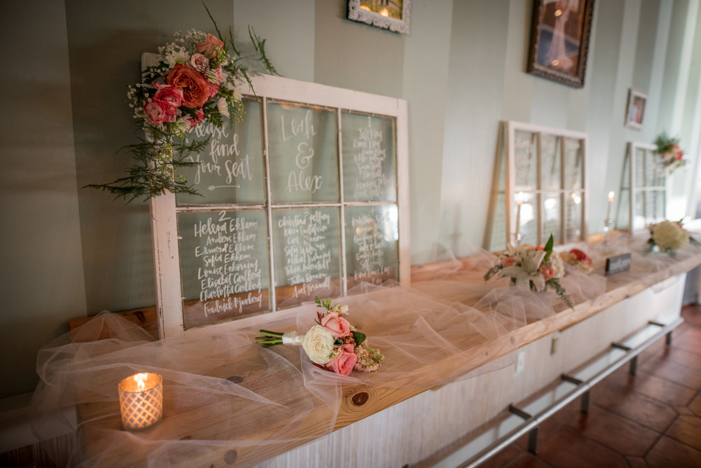 Instead of individual place cards, Leah & Alex wrote their guests' seating locations on beautiful old windows.
