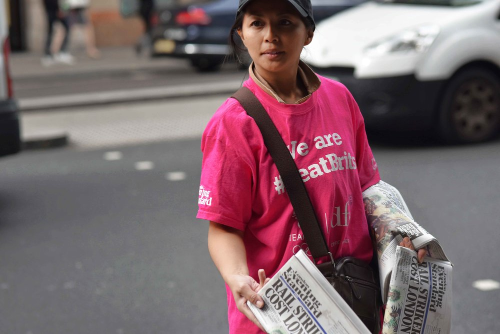 Girl selling newspaper, Kensington High Street, London, U.K. Image©thingstodot.com
