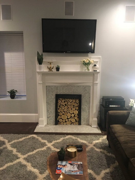 After: Fireplace with the original wood mantle and iron interior and decorative birch wood.