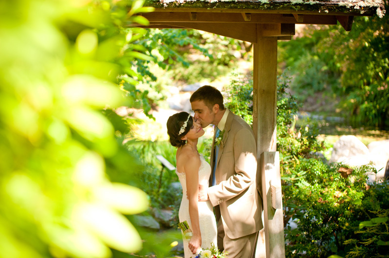 Groom kisses Bride on the cheek under Japanese arbor in Berkeley, CA