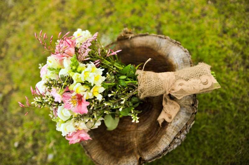 Detail of bridal bouquet on tree stump