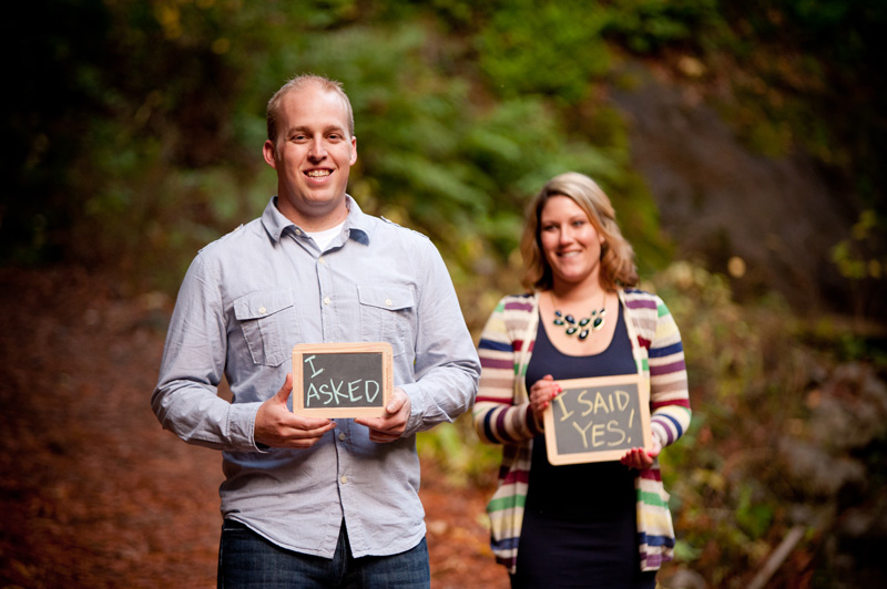 "Couple with chalk boards saying ""I asked"" and ""I said yes"""