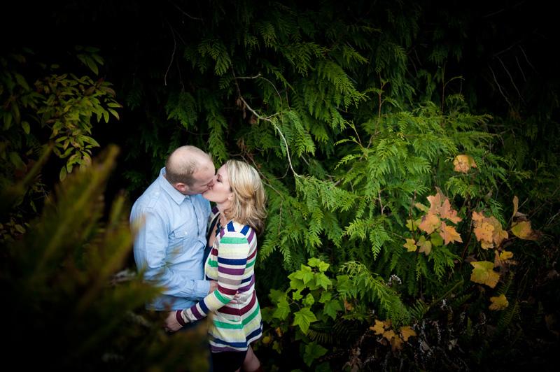 Couple kissing amongst trees
