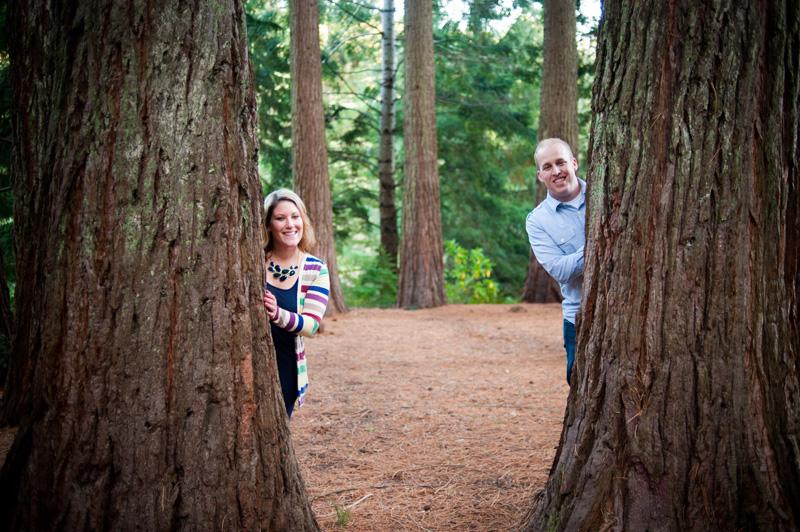 Couple peeking around redwood trees