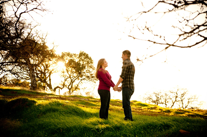 Couple holding hands backlit in grove in Fairfield, CA