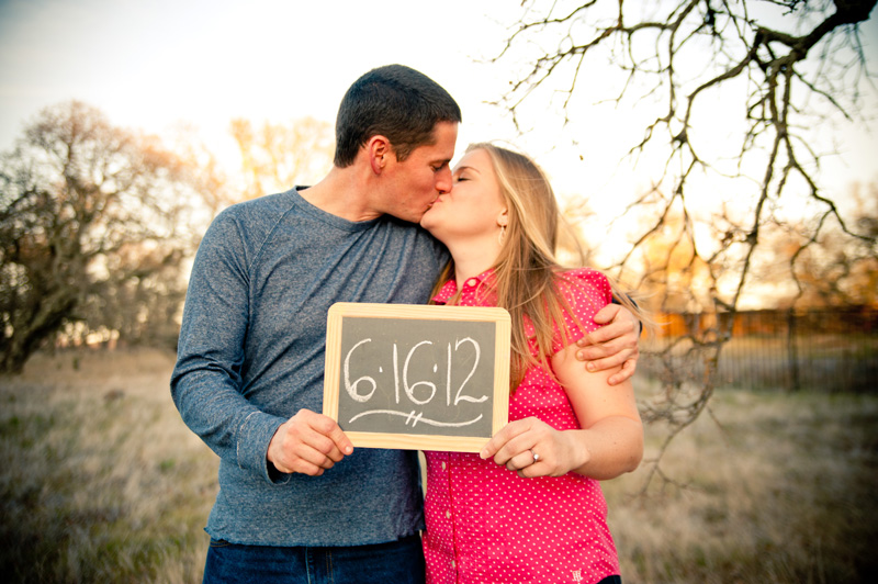 Couple kissing holding chalkboard with save the date in Fairfield, CA