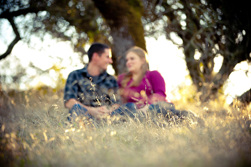 Out of focus couple sitting in tall grass in Fairfield, CA