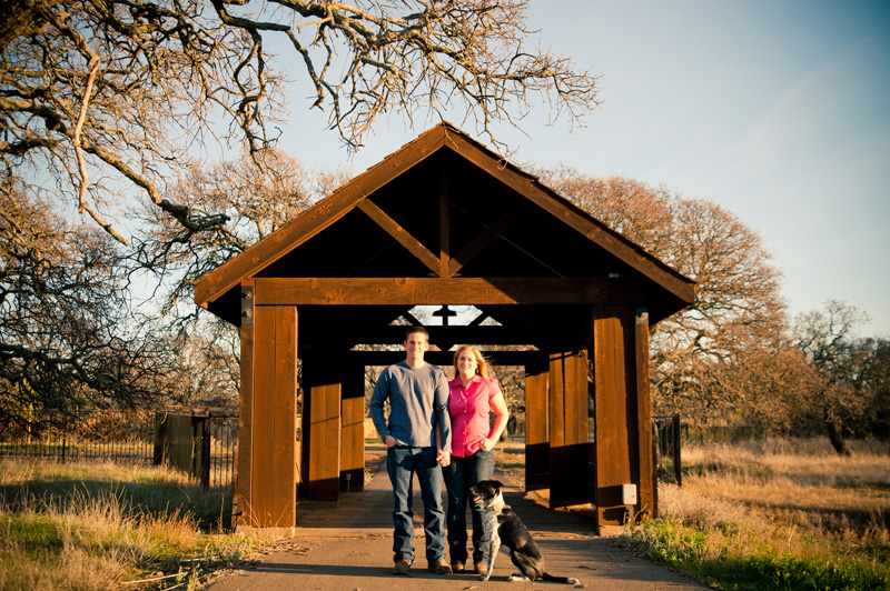 Couple in front of rustic covered bridge in Fairfield, CA