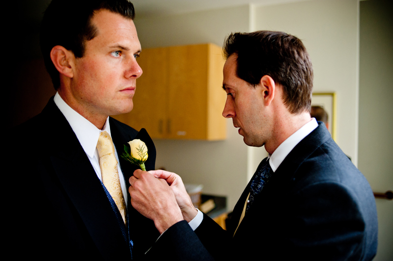Groom applying boutonniere. Piedmont, CA