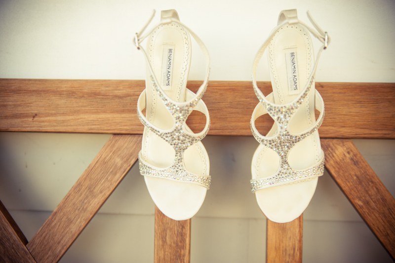 Brides wedding shoes hanging on wooden bench