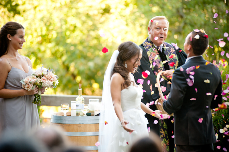 Bride and groom being showered with rose petals