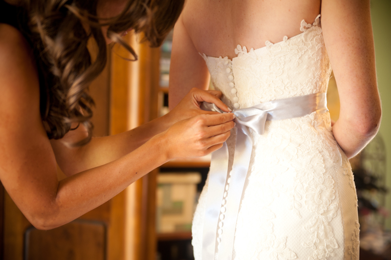 Bridesmaid helping bride with her wedding dress