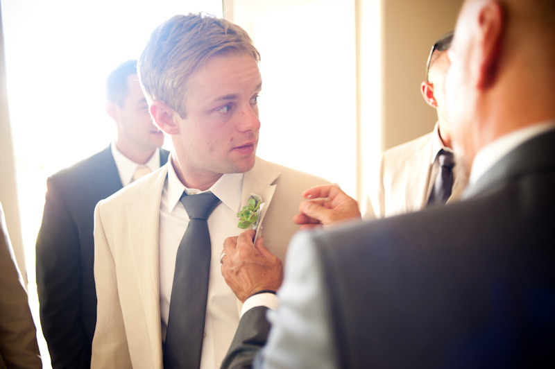 Groomsman having boutonniere applied