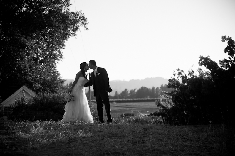 Bride and groom sharing kiss in vinyard