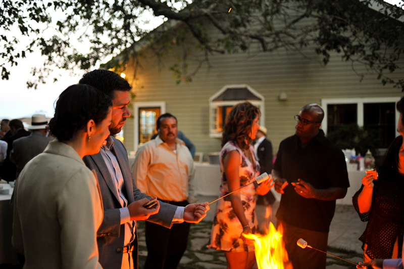 Wedding guests roasting marshmallows over fire pit