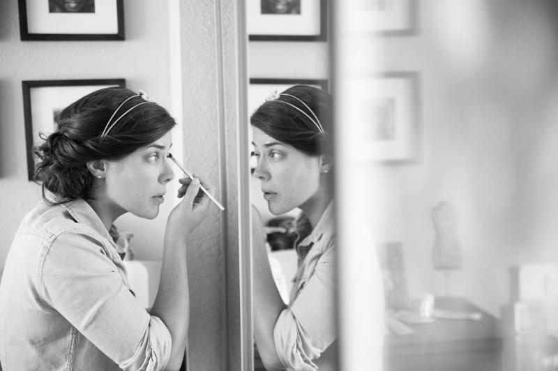 Bride applying makeup in mirror in San Francisco, CA