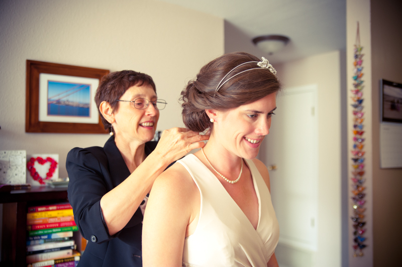 Mother of bride helping with jewelry