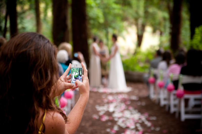 Wedding guest taking photo down the aisle