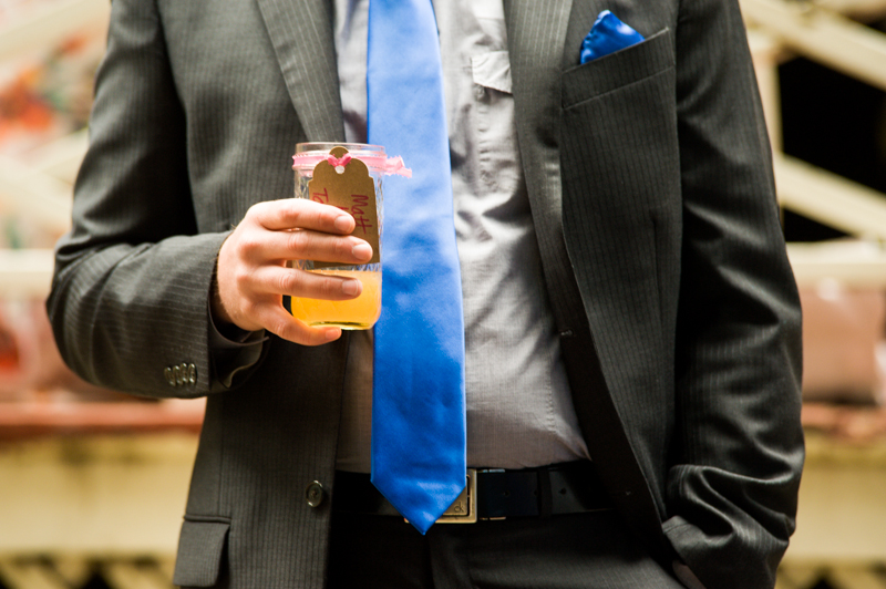 Detail of wedding guest with cocktail and blue tie