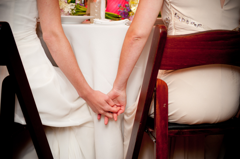 Brides holding hands at reception in Trocadero house