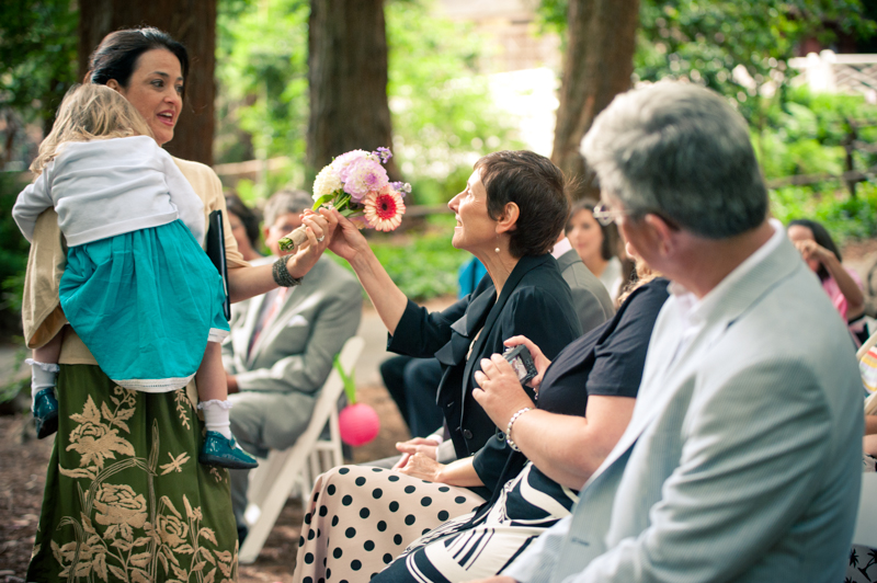 Flower girl giving bouquet to parents