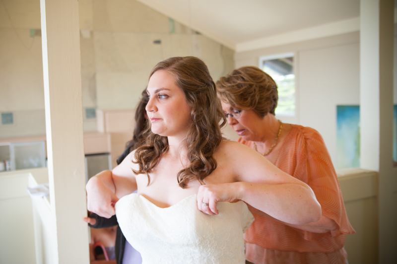 Mother helping bride get into wedding dress