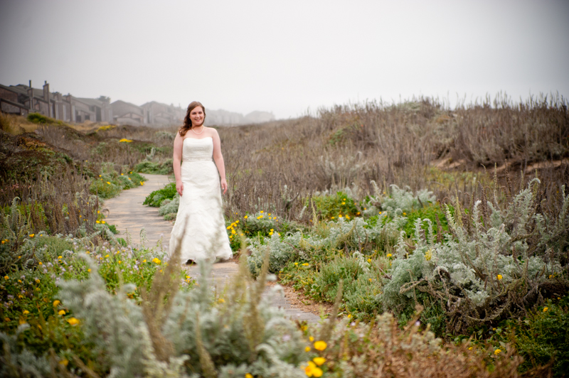 Bride walking on wooden beach path in Monterey, CA