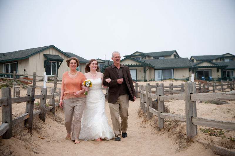 Bride walking down beach path with mother and father