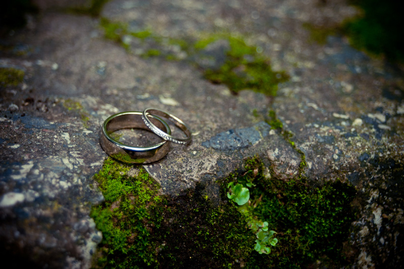 Wedding rings on mossy stone at Lake Temescal wedding