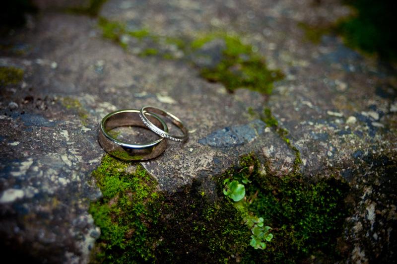 Wedding rings on mossy stone at Lake Temescal wedding