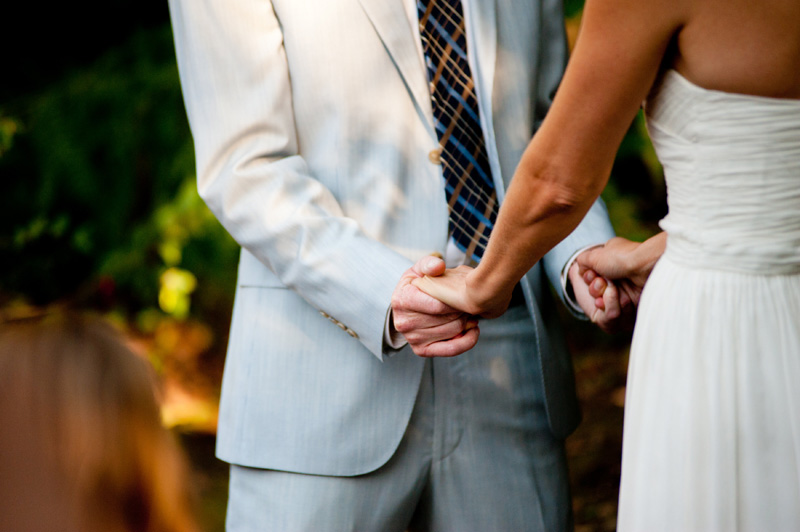 Detail of bride and groom holding hands during wedding ceremony in Oakland, CA
