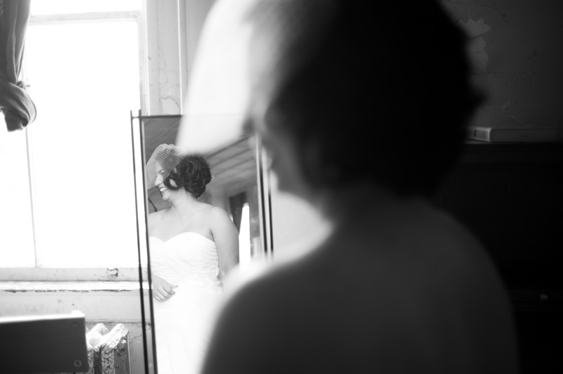 Black and white of bride looking at self in mirror