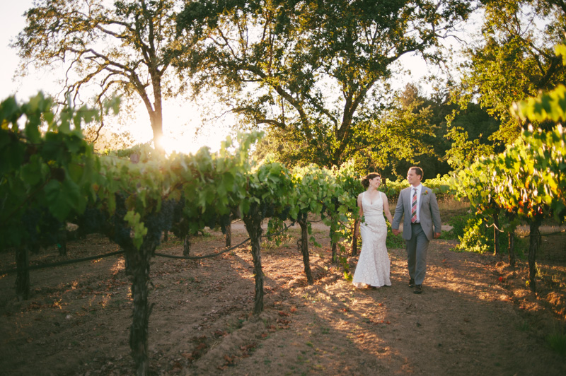 Couple walking through St. Helena vineyard at sunset