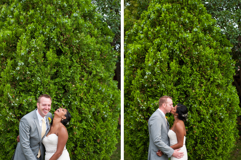Candid portrait of bride and groom in front of evergreen