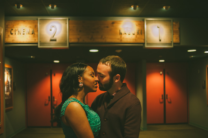 Couple kissing inside movie theater for engagement session